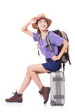 Woman traveler sitting on suitcase with backpack Stock Images