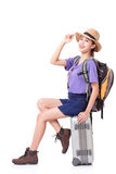 Woman traveler sitting on suitcase with backpack royalty free stock photo