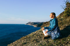 Woman traveler sitting on top of a cliff and looking at sea Royalty Free Stock Photography