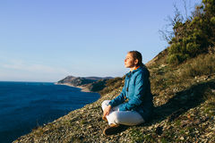 Woman traveler sitting on top of a cliff and looking at sea. Royalty Free Stock Photos