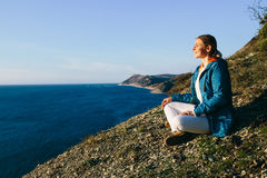 Woman traveler sitting on top of a cliff and looking at sea. Royalty Free Stock Images
