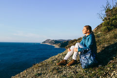Woman traveler sitting on top of a cliff and looking at sea Stock Photo