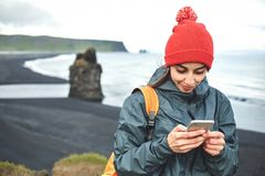 Woman using smartphone on Kirkjufjara black sand beach, southern Iceland. Woman traveler with small orange backpack walking on Kirkjufjara black sand beach and Royalty Free Stock Images