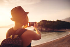 Woman traveler with smartphone taking photo near sea Stock Images