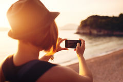 Woman traveler with smartphone taking photo near sea Stock Photo