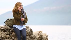 A woman traveler speaks on the phone. A woman traveler with a backpack stands on a rock on the sea coast against the backdrop of the mountains and speaks on the stock footage