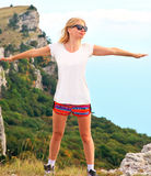 Woman Traveler standing outdoor hands raised to the blue sky with mountains Royalty Free Stock Image