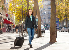 Woman traveler with suitcase along the street Royalty Free Stock Images