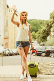 Woman traveler with suitcase waiting for car. Stock Photo
