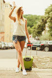 Woman traveler with suitcase waiting for car. Royalty Free Stock Image