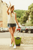 Woman traveler with suitcase waiting for car. Royalty Free Stock Photography