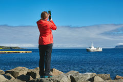 Woman traveler take a photo of ocean in Iceland. Woman traveler in warm clothing take a photo of ocean and ship in Iceland. Travel to Iceland, West Fjords Royalty Free Stock Image