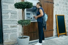 Woman traveler takes out money at an ATM in Europe.  Royalty Free Stock Photography