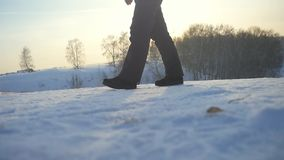 Woman traveler trekking in wintertime cold snowy weather, girls leg walking over natural colorful sunset sky in slow stock footage
