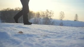 Woman traveler trekking in wintertime cold snowy weather, girls leg walking over natural colorful sunset sky through the stock video footage