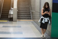 Woman traveler use smartphones to find travel maps at subway. In Bangkok stock photography