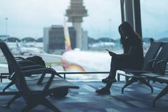 A woman traveler using mobile phone in the airport. A woman traveler using mobile phone while sitting in the airport stock image