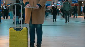 Woman traveler using pad at the airport. Slow motion of a woman with trolley bag using touch pad in crowded airport or station hall stock footage