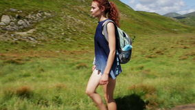Woman traveler is walking through the mountains and forests stock video footage