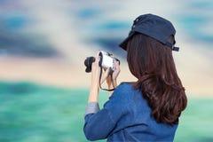 Woman traveler wearing blue dress as photographer, take photo wi Stock Photography