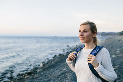 Woman traveler in a white clothing standing on the shore and looks at sea Stock Image