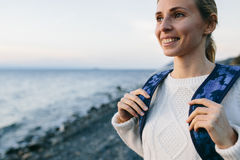 Woman traveler in a white clothing standing on the shore and looks at sea Stock Photo