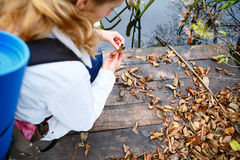 Woman traveler on a wooden platform in the autumn river Royalty Free Stock Photo