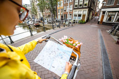 Woman traveling in Amsterdam. Woman riding a bicycle with tourist map on the street in Amsterdam city. View on the hands holding map Stock Photography