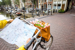 Woman traveling in Amsterdam. Woman riding a bicycle with tourist map on the street in Amsterdam city. View on the hands holding map Stock Image
