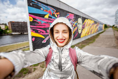 Woman traveling in Berlin. Young woman tourist making selfie photo standing in front of the Berlin wall in Germany royalty free stock photography