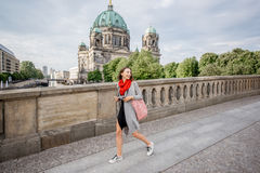 Woman traveling in Berlin. Young woman tourist with photo camera enjoying traveling in Berlin city walking on the old bridge near the famous cathedral Royalty Free Stock Photos