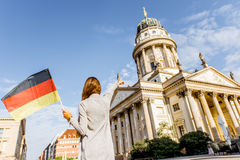 Woman traveling in Berlin. Young woman tourist standing back with german flag on the Gendarmen square with French church and Opera house on the background in Royalty Free Stock Photography