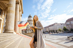 Woman traveling in Berlin. Young woman tourist walking with german flag on the stairs near the Concert house in Berlin Stock Photo