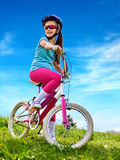 Woman traveling bicycle on green grass in summer park. Stock Photos