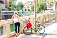 Woman traveling with bicycle in Ljubljana city. Young female tourist standing near the bicycle in Ljubljana city, traveling in Slovenia. Back view with copy royalty free stock images