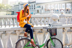 Woman traveling with bicycle in Ljubljana city. Young female traveler sitting with bicycle and using smart phone on the Triple bridge in Ljubljana. Traveling in Stock Images