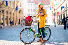 Woman traveling with bicycle in Ljubljana city. Young female traveler standing with bicycle and using smart phone in the old city center in Ljubljana. Traveling stock images