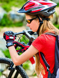Woman traveling bicycle summer park. Girl with smart watch traveling Stock Image