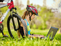 Woman traveling bicycle in summer park. Girl watch laptop. Woman traveling bicycle in summer park. Bicyclist girl watch on laptop. Girl counts pulse after sport Stock Images