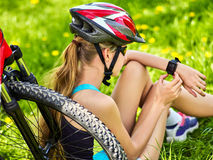 Woman traveling bicycle in summer park. Girl watch smart watch. Woman traveling bicycle in summer park. Bicyclist girl watch on smart watch. Girl counts pulse Stock Photos