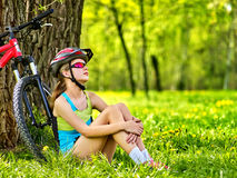 Woman traveling bicycle in summer park. Girl watch smart watch. Woman traveling bicycle in summer park. Bicyclist girl watch on smart watch. Girl counts pulse Royalty Free Stock Photo