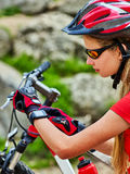 Woman traveling bicycle in summer park. Girl watch smart watch. Royalty Free Stock Image