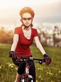 Woman traveling bicycle in summer park. Royalty Free Stock Images