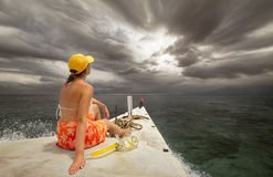 Woman traveling by boat among the islands before rain. Royalty Free Stock Image