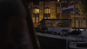 Woman traveling by boat in night Amsterdam and taking photos. Woman tourist enjoying water tour in night Amsterdam and taking city photos with smart phone. Shot stock video footage