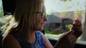 A woman is traveling in a car in the passenger's seat. Uses a smartphone on the road, outside the window is a typical stock video