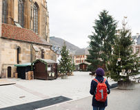 Woman traveling at Christmas Market Alsace, France. THANN, FRANCE - DEC 12, 2015: woman walking in the village of Thann empty Christmas market early in the Stock Photos