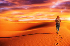 Woman traveling in the desert. Active woman trekking along desert, walking alone in the dune, discovering nature, expedition to the wilderness, travel and royalty free stock photos