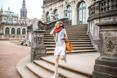 Woman traveling in Dresden city, Germany. Portrait of a stylish woman walking with headphones and bag at the old town of Dresden city, Germany stock photo