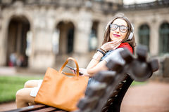 Woman traveling in Dresden city, Germany. Woman sitting with headphones and bag on the bench at the old town of Dresden city in Germany royalty free stock photos